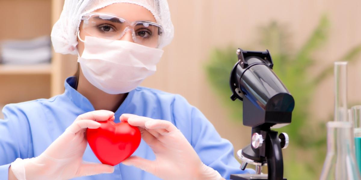 Vrouw in labojas met plastieken hartje in de hand